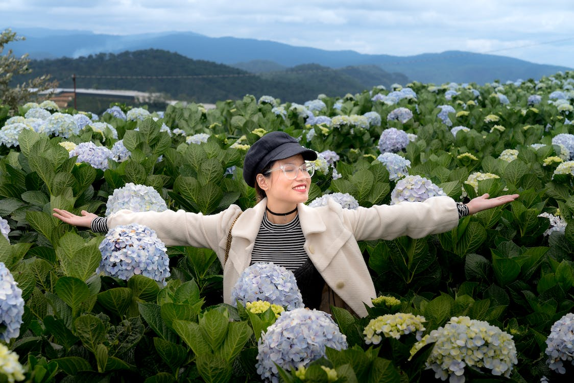 Photo of Smiling Woman in Black Hat, White Coat, and Glasses Standing in Middle of Hydrangea Flower Field With Her Eyes Closed and Hands Stretched Out