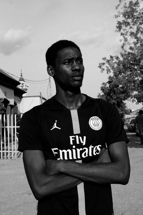 Grayscale Photo of Man in PSG Jersey With His Arms Crossed Looking Away