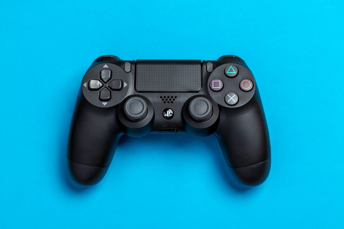 Flat Lay Photo of Black Sony PS4 Game Controller on Blue Background
