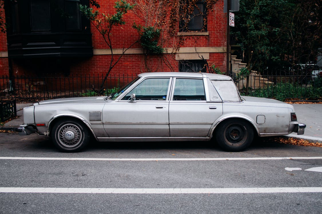 Photo of Silver Sedan Parked Near Red Building