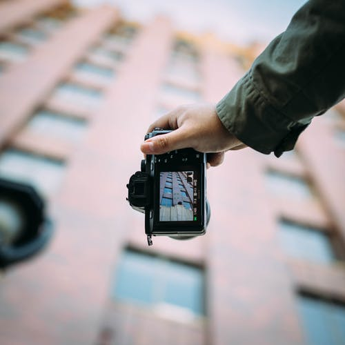Shallow Focus Photography of Person Holding Black Dslr Camera