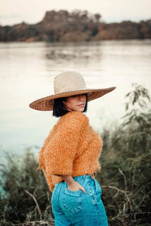 Photo of a Woman in Sun Hat, Orange Knitted Top, and Blue Denim Bottoms