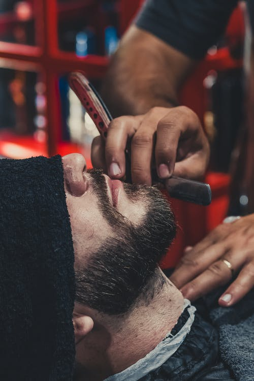 Barber shaving a mans beard