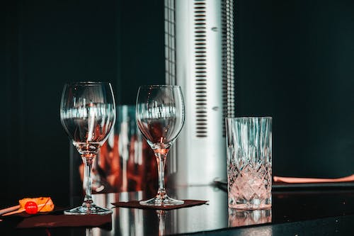 Two Clear Wine Glasses on Brown Table