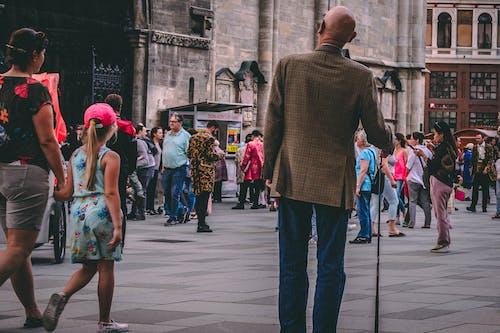 Man in Brown Coat Holding Walking Cane