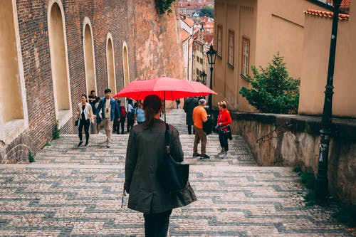 Woman Holding Red Umbrella Walking Towards Staircase