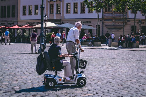 Man And Woman Riding On Mobility Scooter