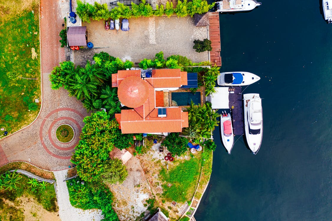 High Angle Photo of Three White boats Beside Brown Building