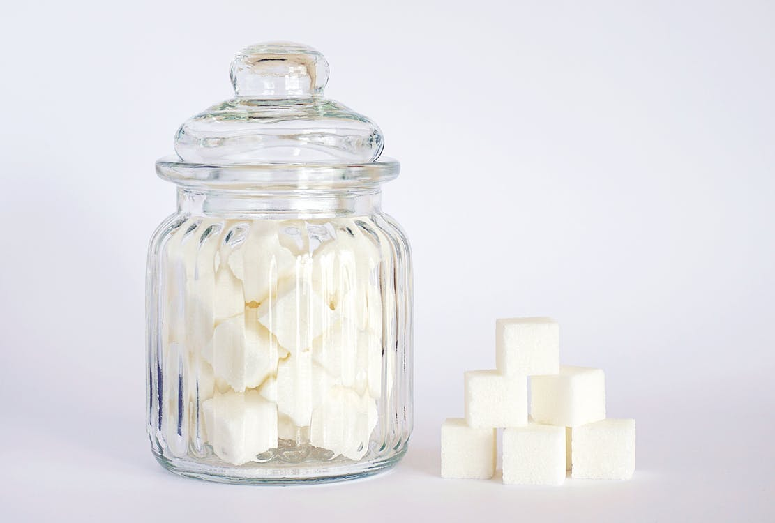 Close-Up Photo of Sugar Cubes in Glass Jar