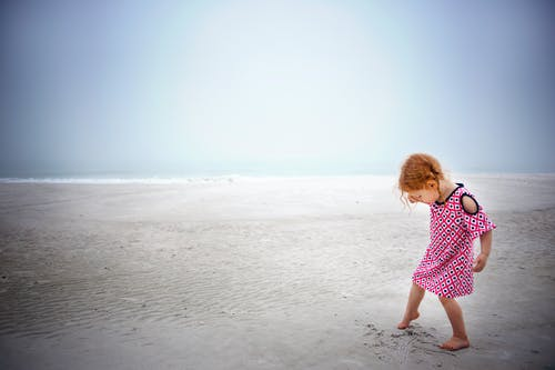 Girl playing on sand near the ocean during day time