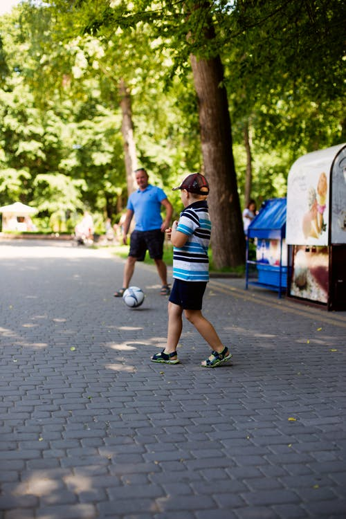 Boy and Man Playing Soccer on the pavement