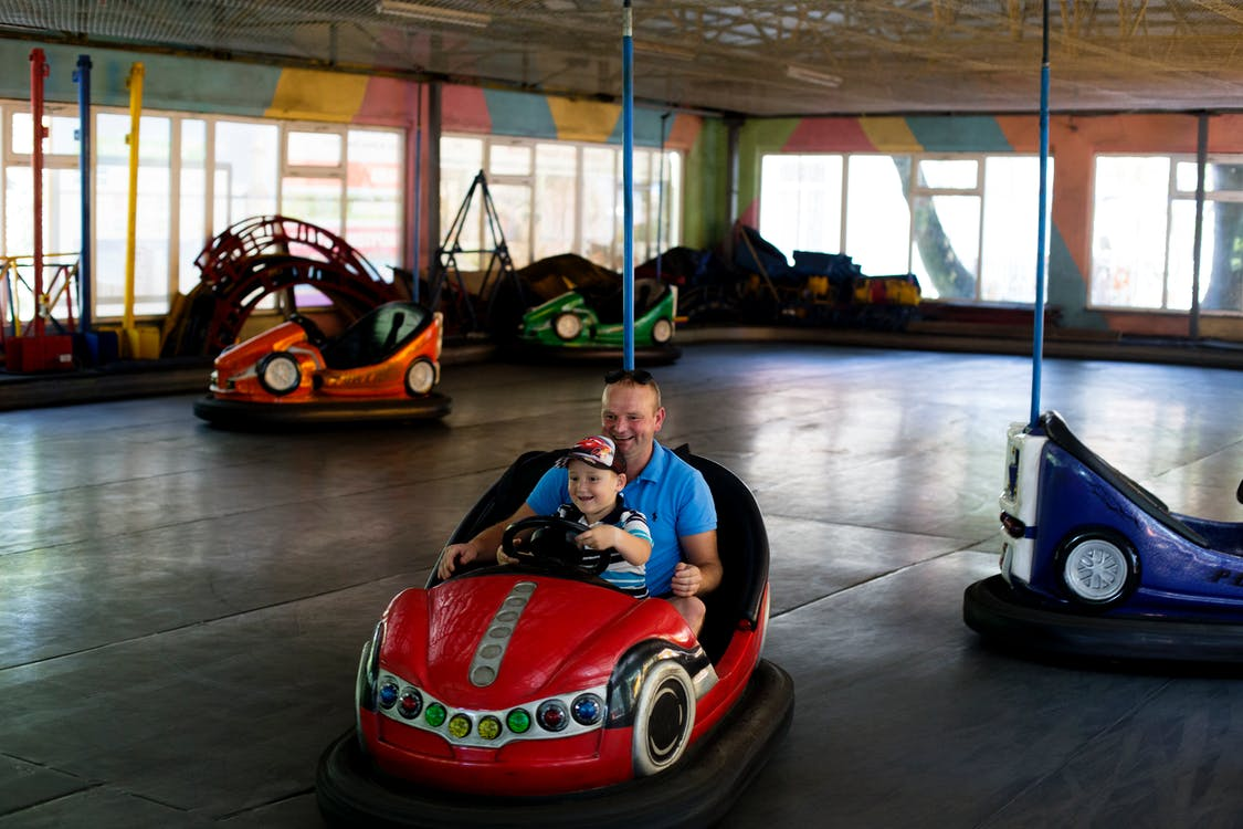 Man and Boy Riding Bumper Car