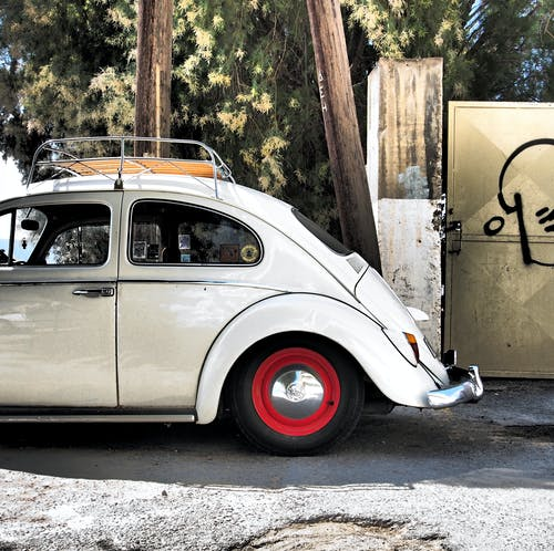 Photo of White Volkswagen Beetle Parked Near Tree