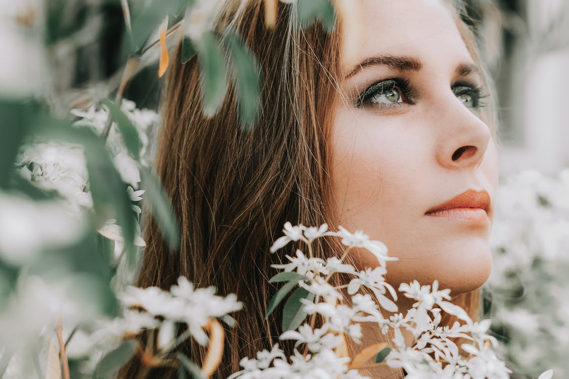 Selective Focus Close-up Photo of Woman's Face Surrounded by White-petaled Flowers