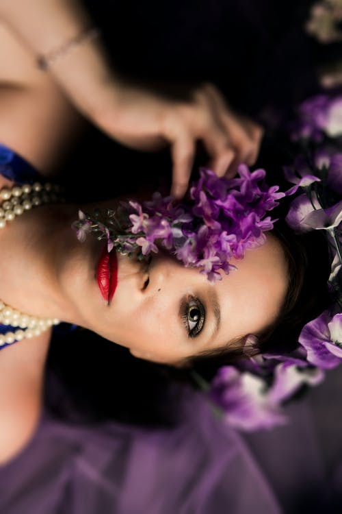 Photography of  Lying Woman Covering Her Eye With Purple Petaled Flowers