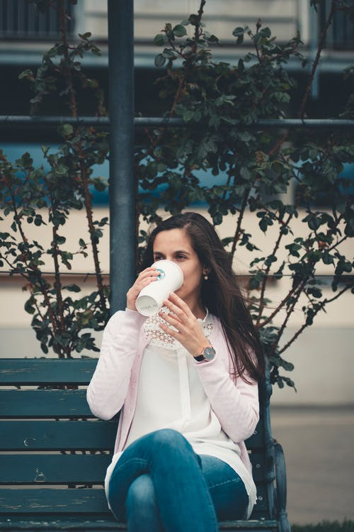 Woman Sitting On Bench While Drinking Coffee