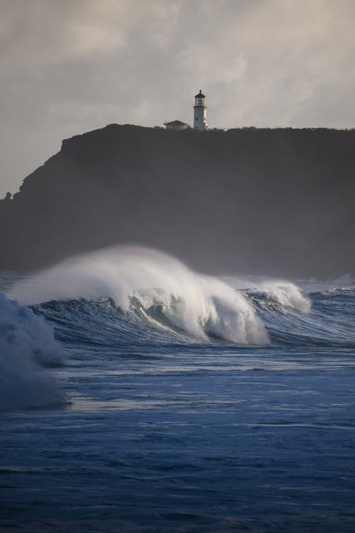 Photography of Ocean Waves Next to Lighthouse on Top of Mountain during Daytme