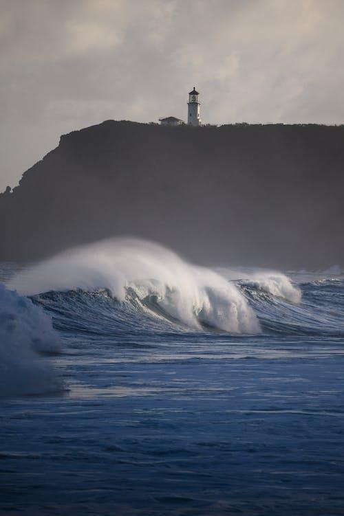 Gratis arkivbilde med bølger, daggry, fyr, hav