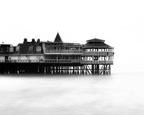 Grayscale Photography of Building on Body of Water