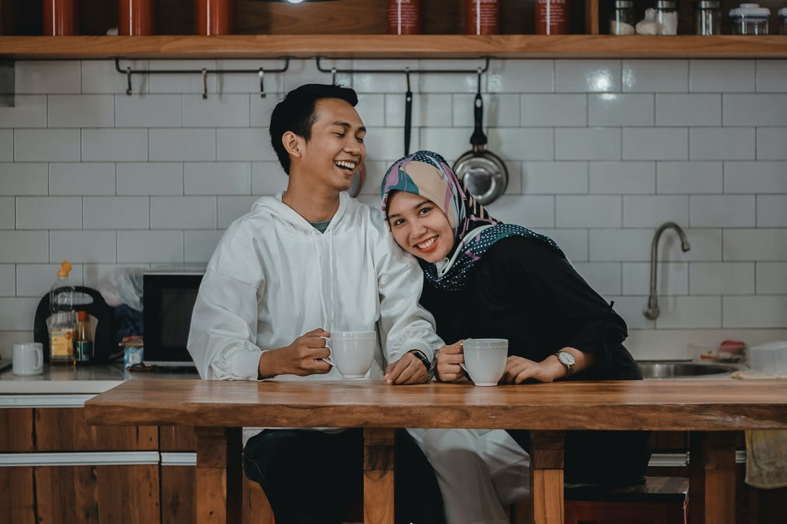 Women Wearing Hijab Leaning on a Man Near a Brown Table