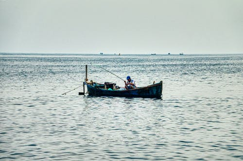Man Sitting on Fishing Boat on Calm Body of Water