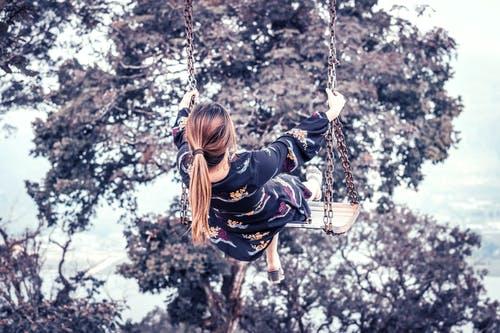 Back view photo of a woman on swinging near a tree