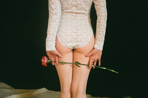 Woman Wearing White Lace Body Suit Holding Rose Flower