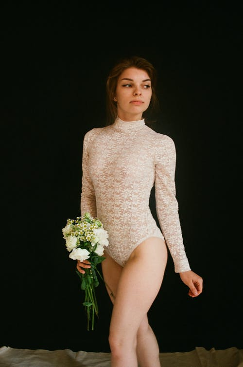 Woman in Body Suit Carrying Flowers