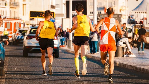 Three People Running in a Road