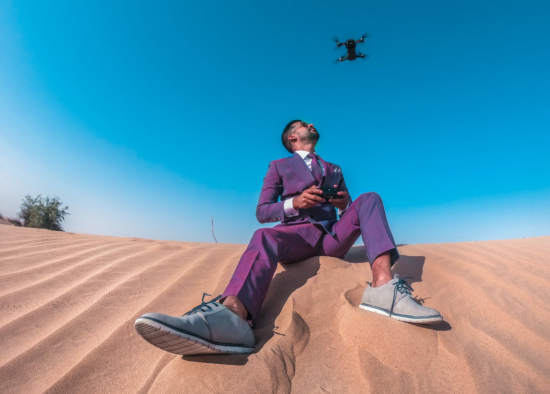 corporate man sitting on the sand while flying his drone