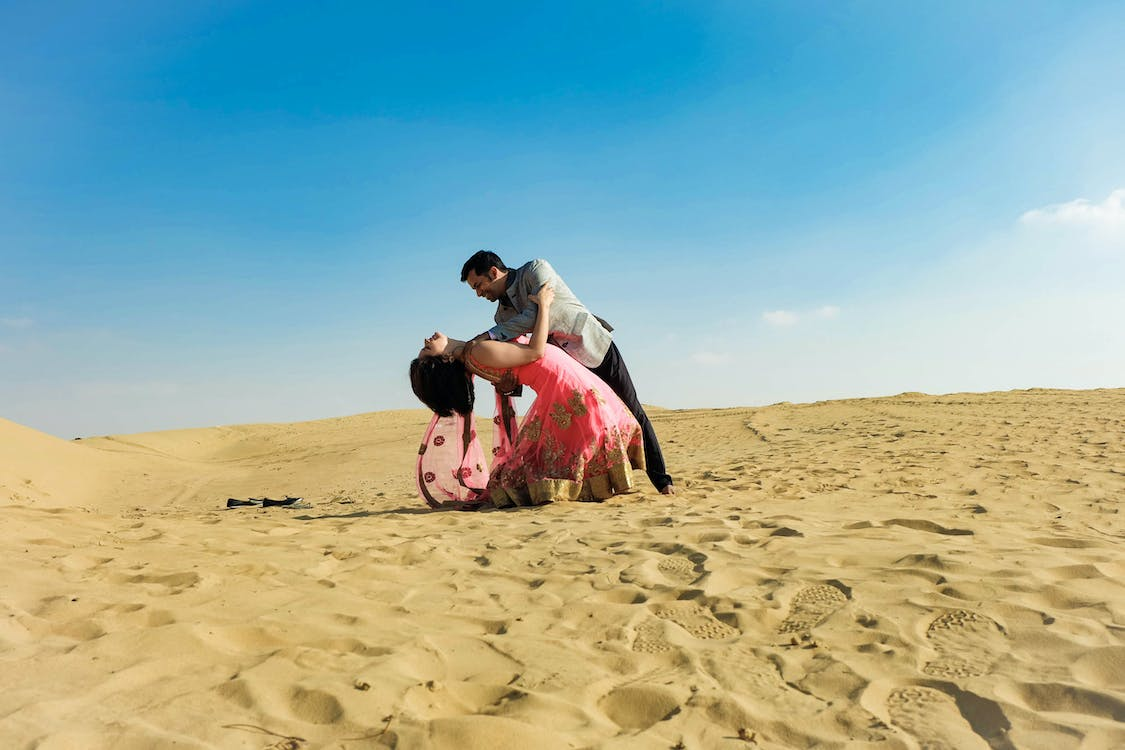 Photo of a Man and Woman Dancing on Desert