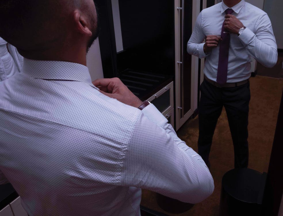 Photo of Man Wearing Dress Shirt While Standing in Front of Mirror
