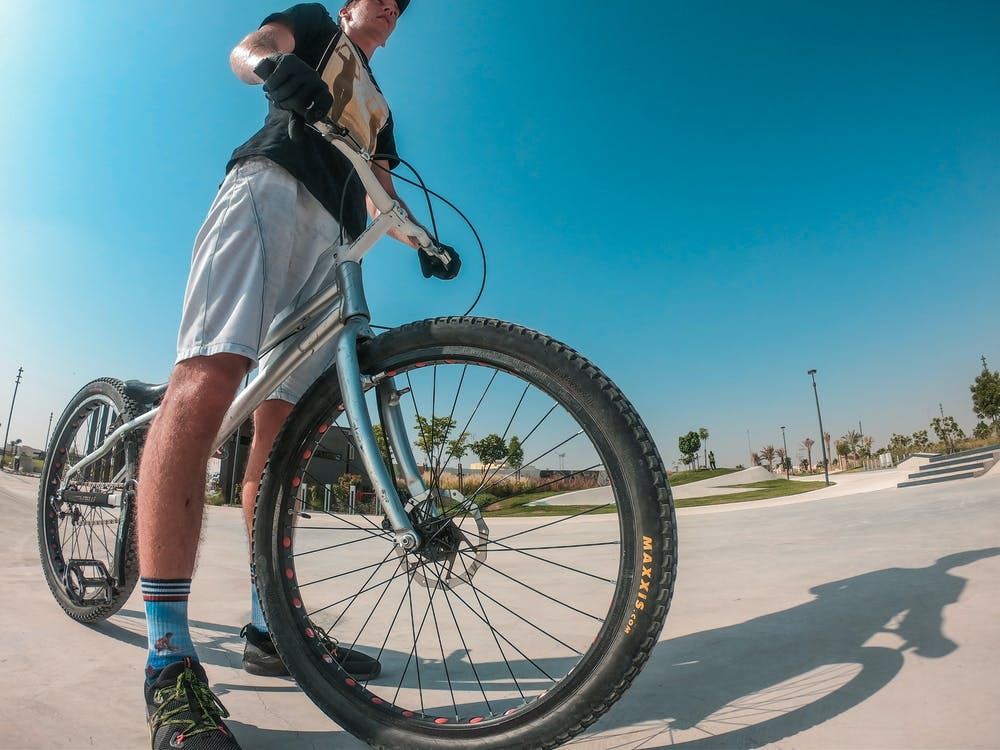 Low Angle Photography of a Man Holding Bike
