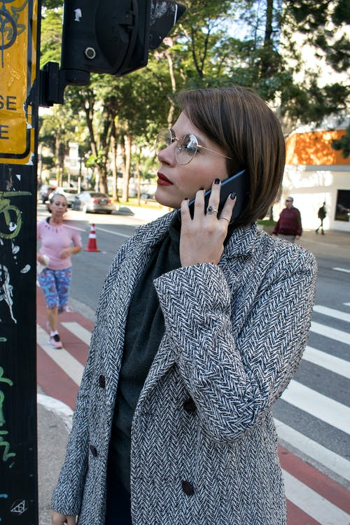 Photo of a Woman Calling Someone With Her Mobile Phone