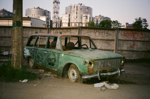 Photo of Abandoned Green Car Beside Post