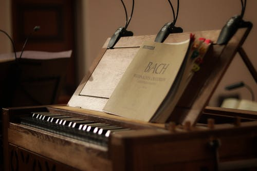 Brown Booklet in a Brown Wooden Piano Close-up Photography