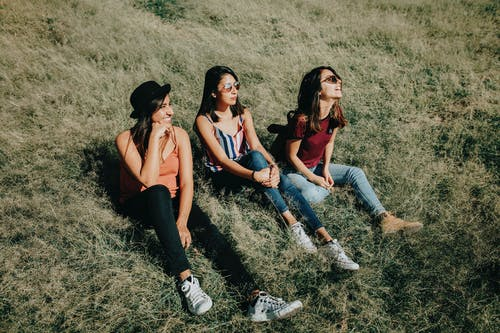 Three Women Sitting On Green Grass