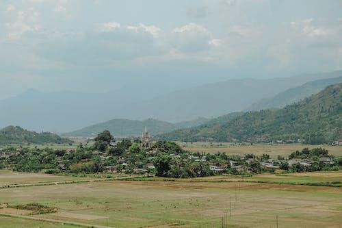 Kostnadsfri bild av berg, dimma, fält, kyrka