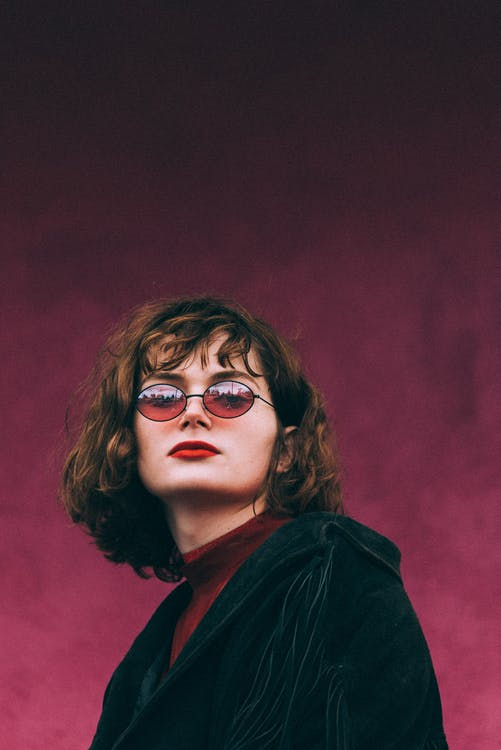 Portrait Photo of Woman in Sunglasses Posing In Front of Purple Background