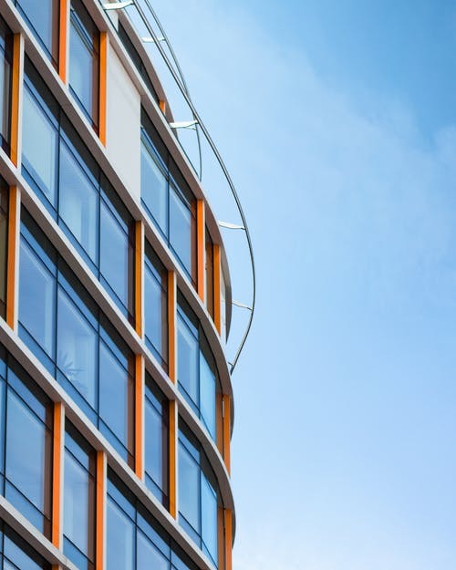 Low Angle Photography of Orange and White Glass-curtain Building