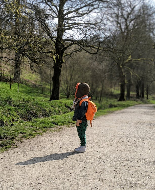 Photo of Child Wearing Backpack Near Bare Trees