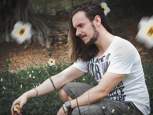 Photo of Man Sitting Beside White Flowers