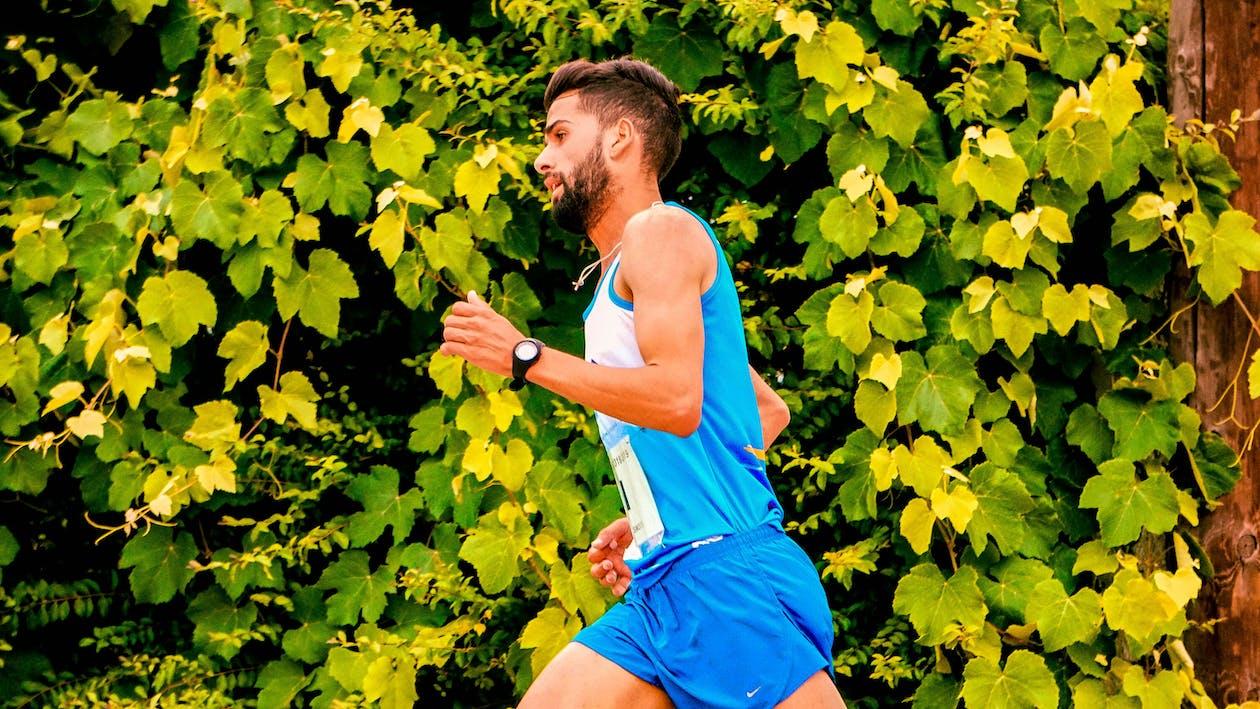 Foto Dell'uomo Che Corre Accanto Alle Piante