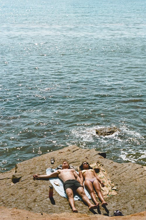 Photo of Couple Lying Down on Cliff Near Sea