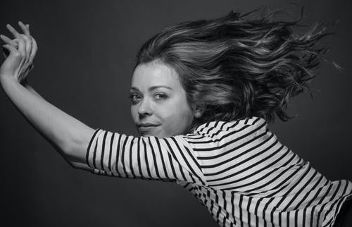 Grayscale Photo of Woman Flipping Hair
