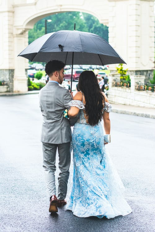 Photo of Couple Walking Under Umbrella