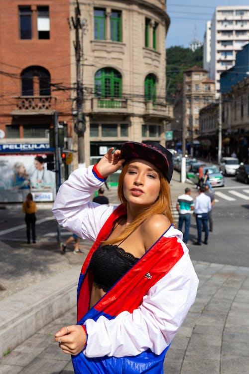 Foto De Mulher Usando Boné Em Pé Na Calçada