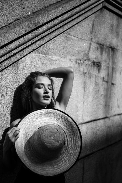 Monochrome Photo of Woman Leaning on Wall While Holding Sun Hat