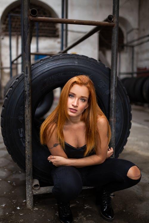 Photo of Woman Sitting Near Tire