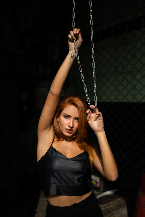 Photo of Woman Wearing Black Crop Top While Holding Chain
